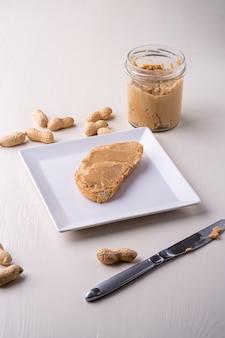 Erdnussbutter-brotsandwich auf nusstabellenmesser der formplatte des weißen quadrats erdnuss