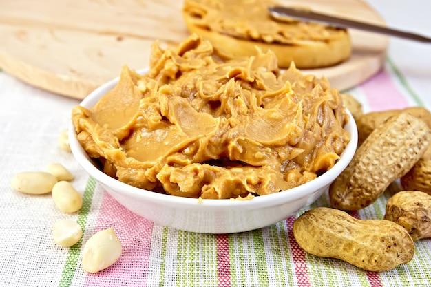 Erdnussbutter in der schüssel, erdnüsse in der schale und gereinigt, brot, messer auf dem hintergrund einer leinentischdecke
