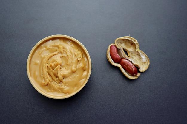 Erdnussbutter in einer runden holzschale auf einem grauen hintergrund