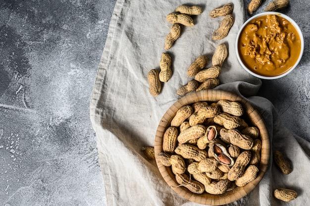 Erdnussbutter in einer schüssel, rohe erdnüsse. vegetarisches essen. grauer hintergrund. draufsicht. platz für text
