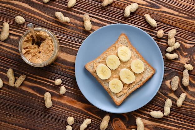 Erdnussbutter-toast mit bananenscheiben auf holztisch