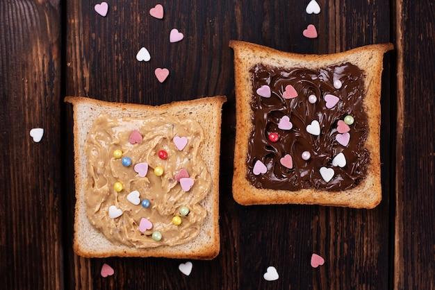 Erdnussbutter und schokoladenpaste auf toast bestreut mit bunten herzen auf dunklem holzhintergrund.