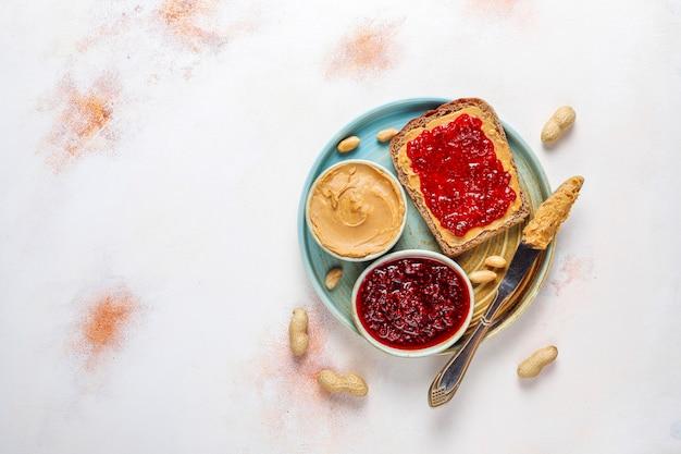 Erdnussbuttersandwiches oder toast mit himbeermarmelade.