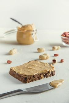 Erdnusspaste auf braunem vollkornbrot. gesunde ernährung.