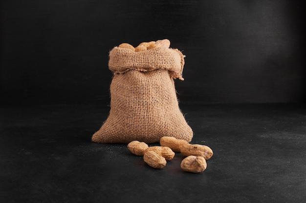 Erdnussschalen aus einem rustikalen paket auf schwarzem hintergrund.