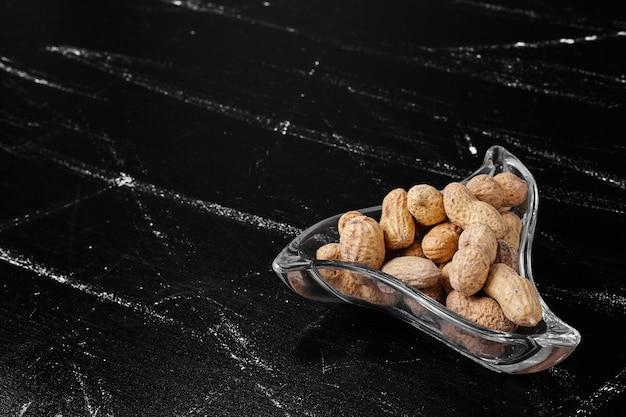 Erdnussschalen in einer glasschale.