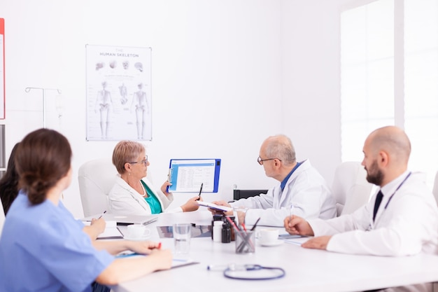 Erfahrene ärzte im besprechungsraum des krankenhauses, die während des gesundheitsseminars zusammenarbeiten. klinik-expertentherapeut im gespräch mit kollegen über krankheit, mediziner