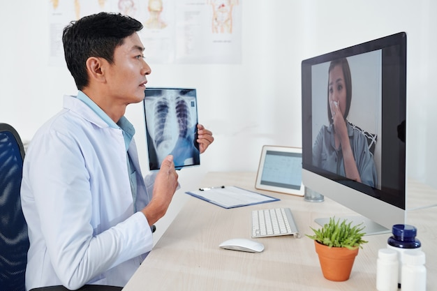 Erfahrene ärztin, die einen videoanruf mit der patientin hat, ihre röntgenaufnahme der brust zeigt und die empfohlene therapie erklärt