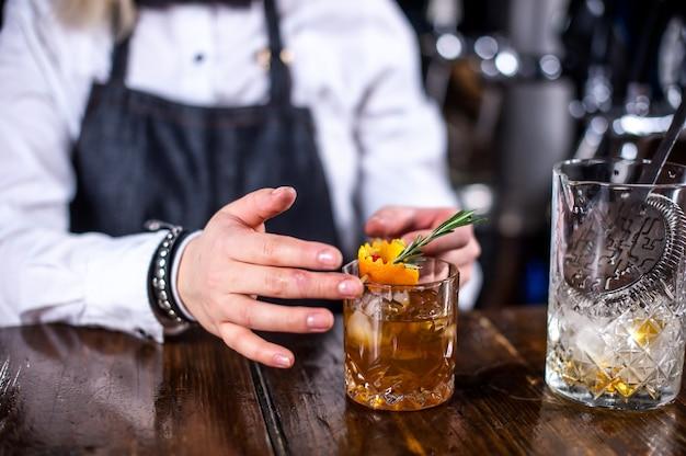 Erfahrene bardame gießt ein getränk ein, während sie in der nähe der bartheke in der bar steht