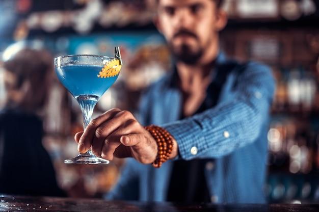 Erfahrene barkeeper, die im nachtclub frisches alkoholisches getränk in die gläser gießen
