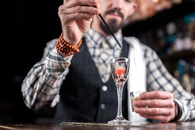 Erfahrene barkeeperin macht einen cocktail an der bar