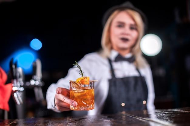 Erfahrene barkeeperin mixt im nachtclub einen cocktail