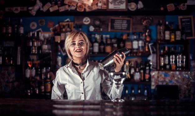 Erfahrene barmannin formuliert einen cocktail im nachtclub