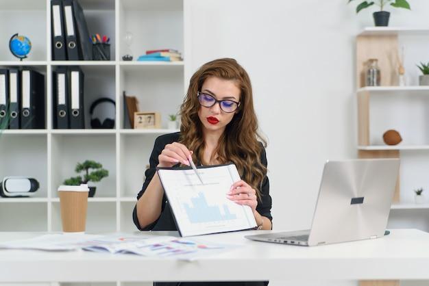 Erfahrene erfolgreiche geschäftsdame in stilvollen kleidern und brillen im gespräch mit ihrem geschäftspartner per videoanruf und zeigt bericht mit grafiken.