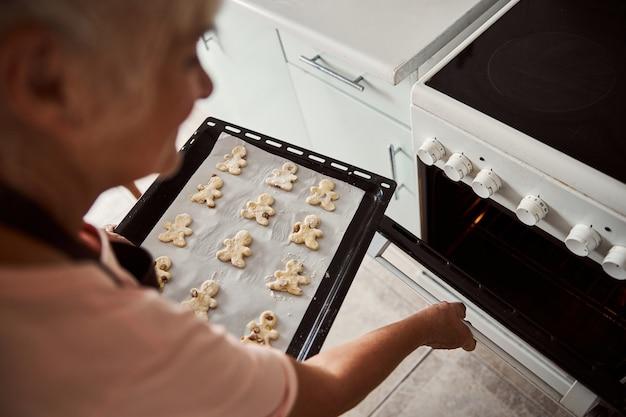 Erfahrene frau im alter, die ein paar kekse backen will