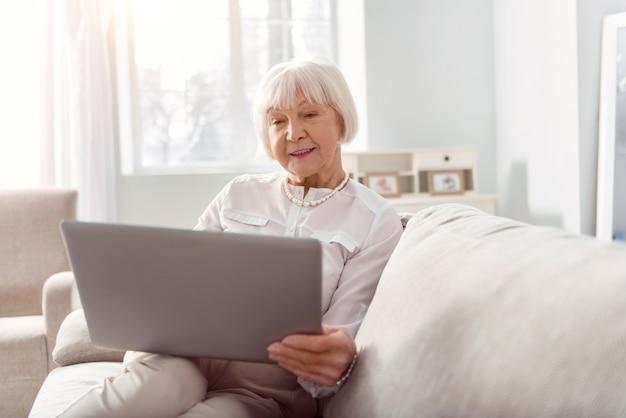 Erfahrene geschäftsfrau. angenehme optimistische ältere frau, die auf dem sofa sitzt und eine geschäfts-e-mail auf ihrem laptop liest, während sie lächelt