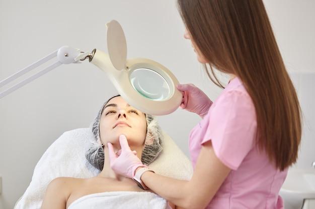 Erfahrene junge kosmetikerin im rosa laborkittel, der lupe in einer hand hält.