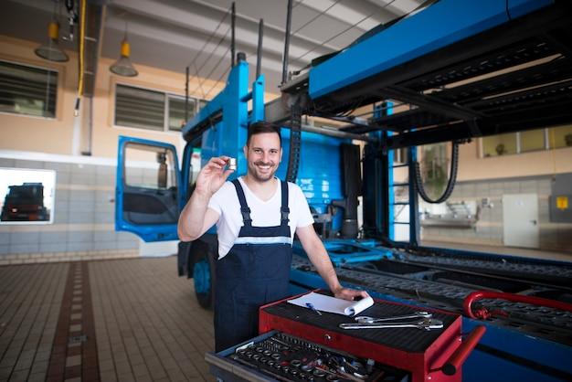 Erfahrene lkw-mechaniker mittleren alters, die teile und werkzeuge in der werkstatt am lkw halten