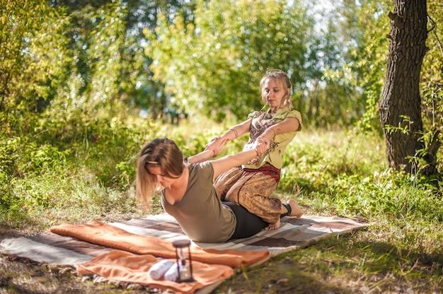 Erfahrene masseurin wendet ihre massagefähigkeiten auf ihren klienten auf dem waldboden an.