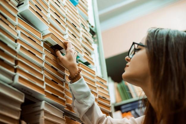 Erfahrene professionelle attraktive bibliothekarin, die ein buch für einen leser nimmt