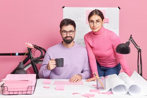 Erfahrene professionelle büroangestellte arbeiten zusammen, um architektenprojekte durchzuführen, brainstorming zusammen durchzuführen, posieren auf dem desktop mit blaupausen, papieren und skizzen haben eine kaffeepause. kollegen designer