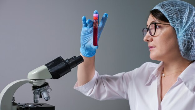 Erfahrene wissenschaftlerin mit brille betrachtet eine probe roter flüssigkeit im reagenzglas in der nähe des mikroskops, das in einem modernen krankenhaus in der nähe arbeitet