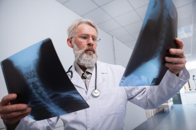 Erfahrener älterer männlicher radiologe, der röntgenaufnahmen der wirbelsäule eines patienten betrachtet