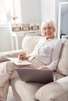 Erfahrener arbeiter. charmante fröhliche ältere frau, die auf dem sofa sitzt und an ihrem laptop arbeitet und wirtschaftsforschung durchführt