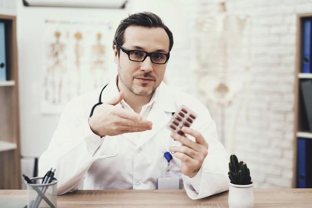 Erfahrener arzt mit stethoskop und packung tabletten.