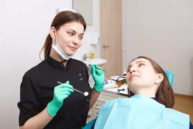 Erfahrener attraktiver junger brünetter zahnarzt, der zahnärztliche werkzeuge hält, während zähne der patientin auf hohlräume überprüft