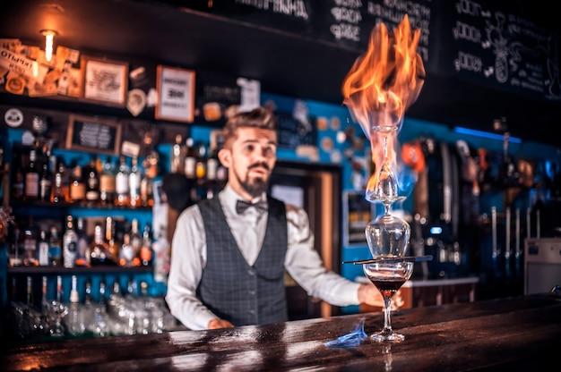 Erfahrener barkeeper, der im nachtclub frisches alkoholisches getränk in die gläser gießt