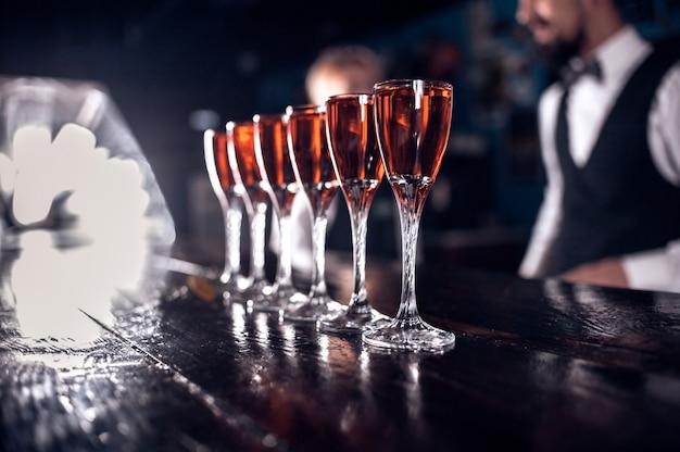 Erfahrener barmann, der frisches alkoholisches getränk in die gläser in der kneipe gießt