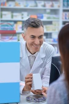 Erfahrener beratender apotheker, der einem kunden ein neues medikament empfiehlt