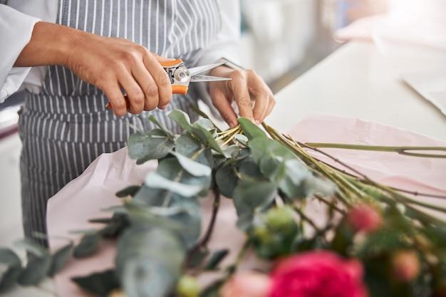 Erfahrener florist, der blumen vor dem anfertigen eines blumenstraußes trimmt