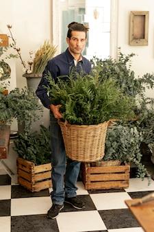 Erfahrener florist, der korb der pflanzen hält