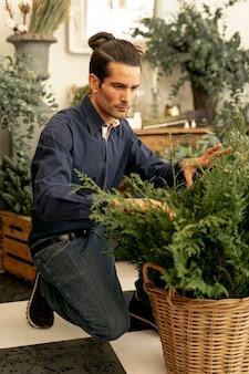 Erfahrener florist, der pflanzen betrachtet