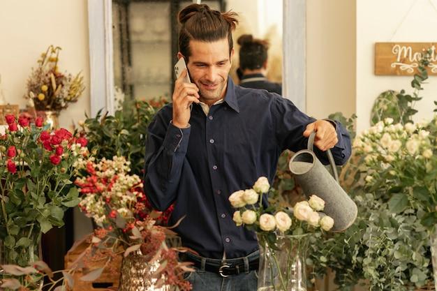 Erfahrener florist, der telefoniert und die pflanzen gießt