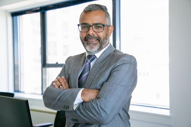 Erfahrener geschäftsmann, der im büroraum steht. mitarbeiter des indischen inhaltsbüros in brillen, die mit gefalteten händen lächeln und posieren. geschäfts-, management- und unternehmenskonzept