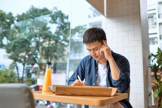 Erfahrener gutaussehender männlicher chefredakteur, der die skriptüberprüfung des jungen autors liest, der fehler im notizbuch korrigiert, während er während der pause kaffee zum frühstück trinkt und die veröffentlichung für den druck in der zeitung vorbereitet