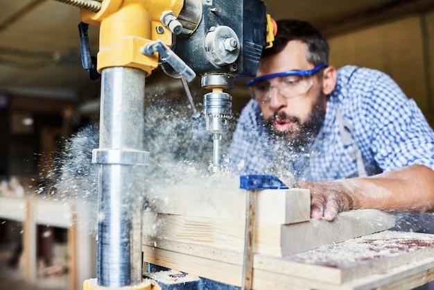 Erfahrener handwerker, der holzmöbel in der tischlerei herstellt