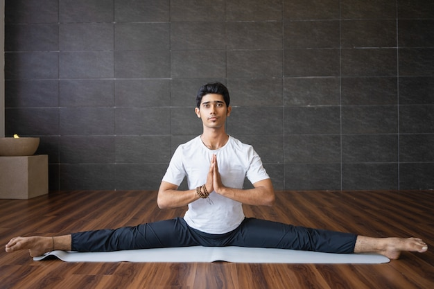 Erfahrener indischer yogi, der sich im studio teilt