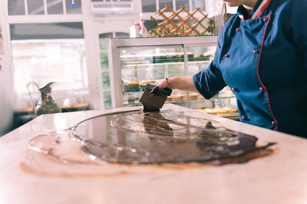 Erfahrener koch. fleißig inspirierter erfahrener koch, der in der küche dunkle schokolade macht