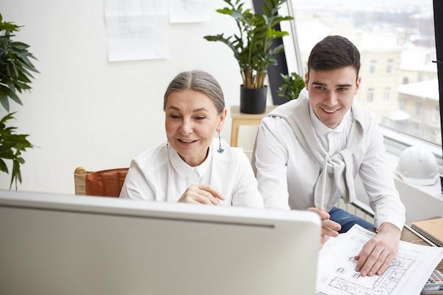 Erfahrener lächelnder reifer weiblicher chefingenieur, der cad-programm auf computer verwendet, während ihr fröhlicher junger männlicher assistent blaupause auf schreibtisch vor ihm studiert. erfolg, teamwork und zusammenarbeit