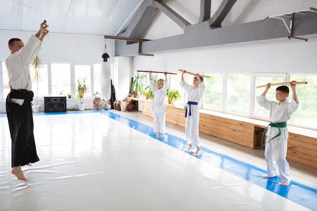 Erfahrener lehrer, der kindern aikido-bewegungen in einem geräumigen lichtzentrum zeigt