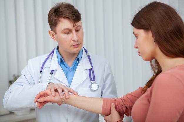 Erfahrener männlicher arzt, der den verletzten arm einer patientin untersucht