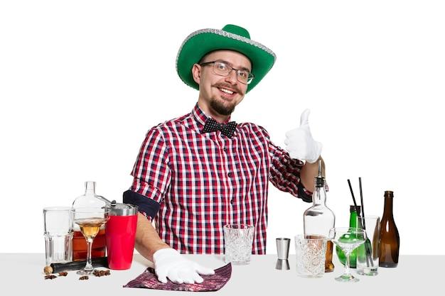 Erfahrener männlicher barmann mit hut macht cocktail an isoliert auf weißer wand. internationaler barmann-tag, bar, alkohol, st. patrick's day-feierkonzept