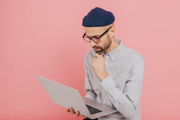 Erfahrener männlicher freiberufler entwickelt neue strategie, hält modernen laptop-computer
