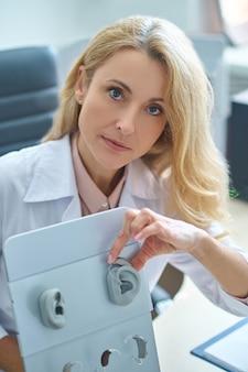 Erfahrener professioneller hno-arzt, der zeigt, wie man ein hörgerät trägt