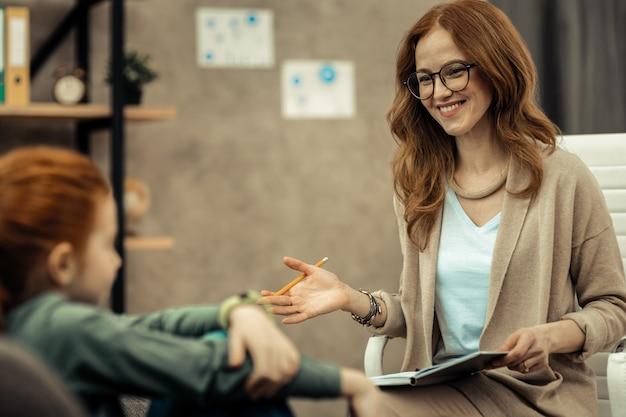 Erfahrener psychologe. intelligente junge frau, die ihre notizen betrachtet, während sie eine sitzung mit einem kind hat