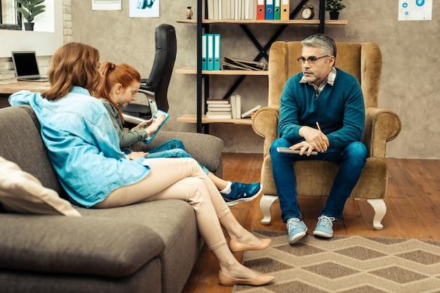 Erfahrener psychotherapeut. kluger intelligenter mann, der seine patienten ansieht, während er eine psychologische sitzung mit ihnen hat